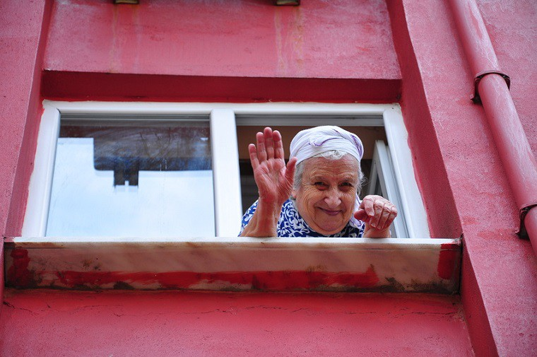 senior woman waving her hand from window